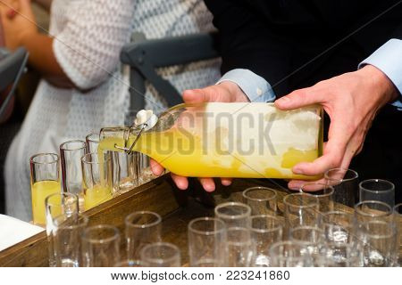 close-up of a waiter serving limoncello in glasses at a party