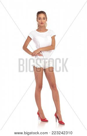 full body picture of a young woman in short pants on white studio background