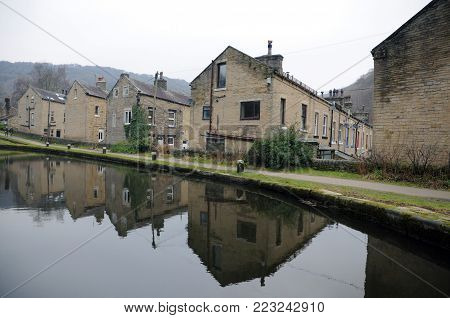 streets of terraced houses alongside the rochdale canal in hebden bridge with buildings reflected in the water in winter