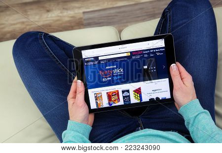 Benon, France - January 21, 2018: Woman sitting cross-legged on her couch using a touch pad to see products on the Amazon website. Amazon.com, Inc. is an American e-commerce company based in Seattle who sales all types of cultural products.