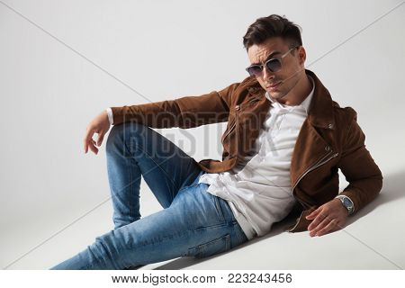 cool fashion man lying down on his elbow on grey background