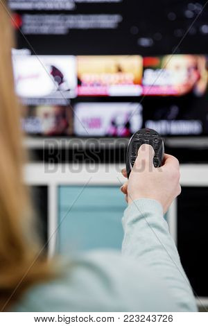 Woman Holding a TV remote control and switching channels on TV set at home