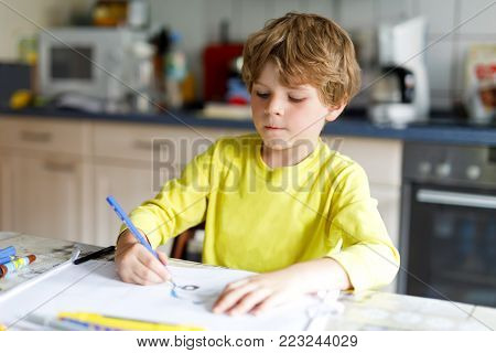 Tired little kid boy at home making homework at the morning before the school starts. Little child doing excercise, indoors. Elementary school and education. Happy blonde kid painting letters and numbers