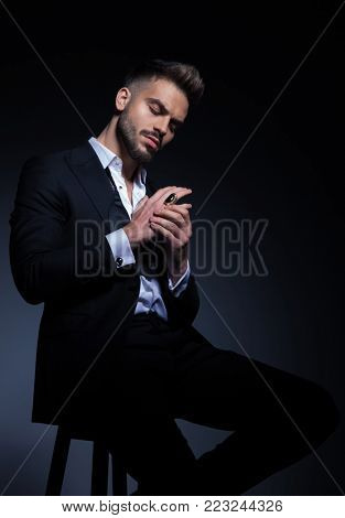 elegant young man in tuxedo holding palms together showing his ring  while sitting on a chair in studio