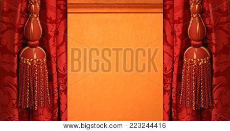 red curtains with magnificent pom-poms on an orange colored background, close-up