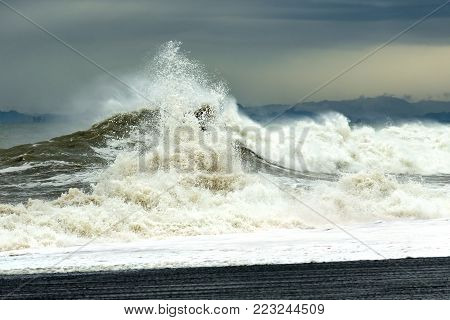 Sea wave with foam and spray during a storm. The concept of tension and struggle.