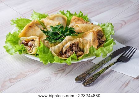 On a light table a white plate with pancakes and mushrooms wrapped in them. Pancakes are laid out in a plate on lettuce leaves and decorated with parsley. Near the plate lie a knife and fork.