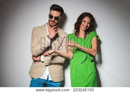 sexy fashion woman laughing while pointing at her man , posing against grey studio background