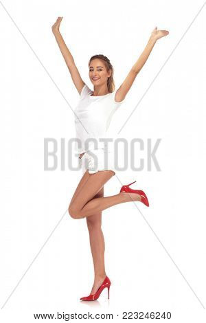 young woman in short pants cheering succes with hands in the air on white studio background