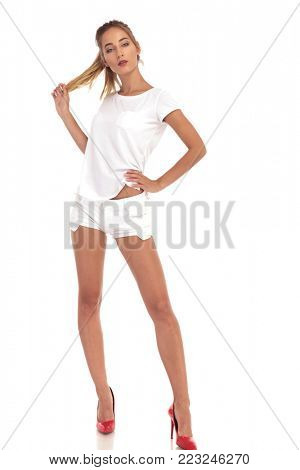 young woman in short pants pulling her hair on white studio background
