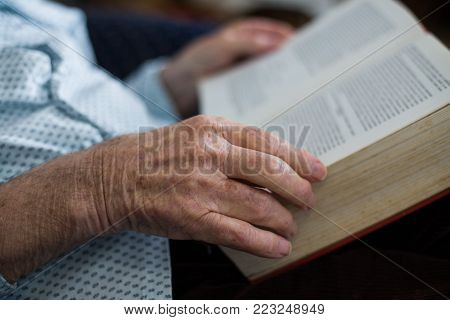 Close up of old man's hands holding book in his lap. Reading literature and continuous learning in 80s.