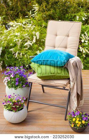 garden chair on terrace in sunlight, flowers bush