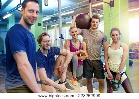 fitness, sport, exercising and healthy lifestyle concept - group of happy people with skipping rope, medicine ball and kettlebell in gym