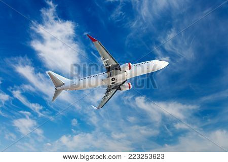 The passenger plane in flight. Aircraft flies high in the blue cloudy sky.