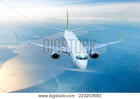 White civil airplane in the sky. Aircraft flying on a high altitude above the plain and the river.