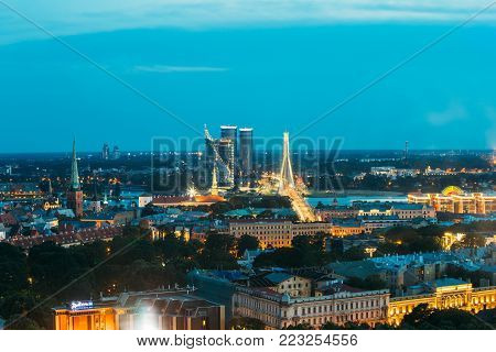 Riga, Latvia - July 2, 2016: Aerial View Of Cityscape In Evening Night Lights Illumination. Castle, President Residence, Swedbank Headquarters, Building Complex Z-towers, Vansu Cable-stayed Bridge