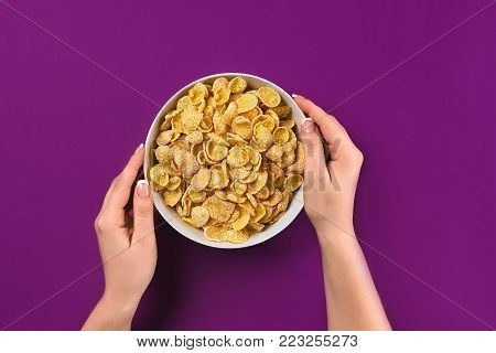 Female hands holding bowl with healthy breakfast, closeup. Bowl with cornflakes on the colorful background. Purple background, top view. Copy space. Still life. Flat lay