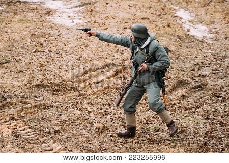 Rogachev, Belarus - February 25, 2017: Re-enactor Dressed As German Wehrmacht Infantry Soldier In WW II Shooting From Handgun