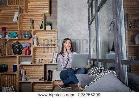 Woman successful writer calling to client via mobile phone while sitting in home interior with laptop computer. Hipster girl talking on cell telephone and working on net-book during recreation time