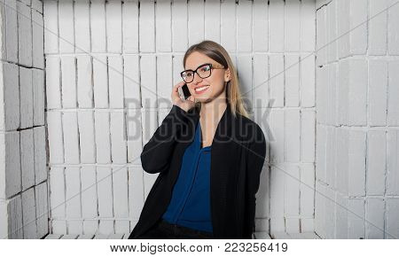 Smiling woman secretary in glasses talking on mobile phone during work break in company. Happy female manager having cell telephone conversation via cell telephone. Hipster girl calling via cellphone