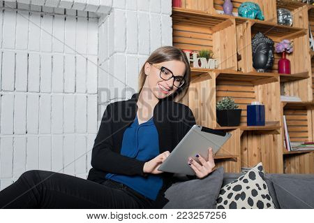 Smiling woman watching funny video in social network via touch pad during free time in holidays sitting in home interior. Cheerful female writer reading article in internet via portable digital tablet