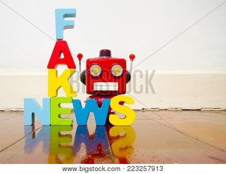 fake news and retro robot head on old wooden floor