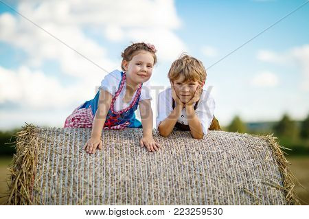 Two kids in traditional Bavarian costumes in wheat field. German children sitting on hay bale during Oktoberfest. Boy and girl play at hay bales during summer harvest time in Germany. Best friends