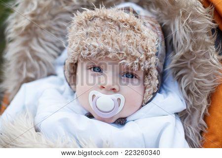 Little baby boy in warm winter clothes and orange pram outdoor