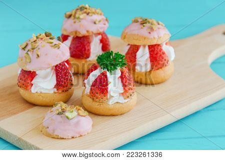 Strawberry choux cream. Combination with choux pastry whipped cream fresh strawberries glaze with white chocolate and chopped pistachios. Sweet and delicious dessert for Valentine. Homemade bakery. Cream puff or choux cream ready to served.