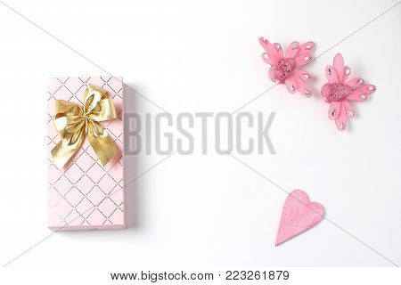 Simple flat lay composition. gift box of pink color with a bow of gold , a decoration in the form of a heart covered with a glitter, two beautiful figures of birds