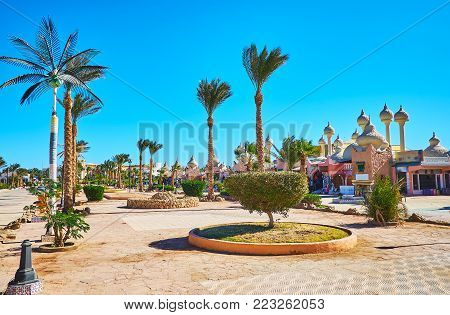 The scenic park with palms and trimmed bushes stretches along 1001 nights market (Alf leila wa leila Bazaar), Sharm El Sheikh, Egypt. poster