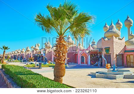 The walk in park with green palms with a view on modern pavilions of Alf leila wa leila (1001 nights) bazaar, Sharm El Sheikh, Egypt. poster