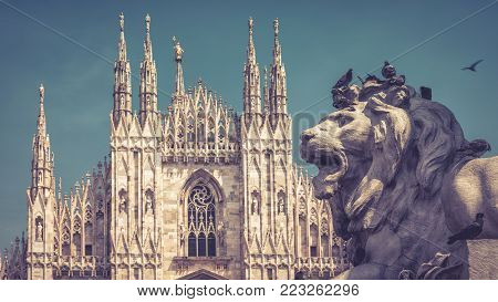Sculpture of a lion as part of monument to Victor Emanuel II in the Piazza del Duomo in Milan, Italy. The Milan Cathedral (Duomo di Milano) in the background.