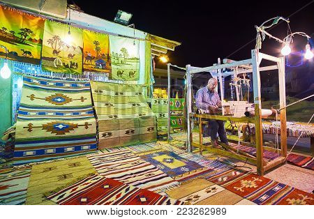 SHARM EL SHEIKH, EGYPT- DECEMBER 15, 2017: The craftsman in the open air workshop in Sharm Old Naama Bay market weaves a rug, using traditional weaving machine, on December 15 in Sharm El Sheikh.