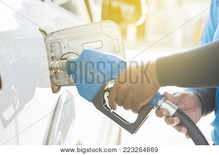 Filling gas at the station. Refill oil, gasoline, diesel vehicle.Hand refilling the car with fuel.