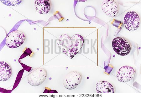 Easter composition with heart, painted eggs, sequins and silk ribbons on a white background. Space for a greeting text. Easter, spring concept. Flat lay, top view