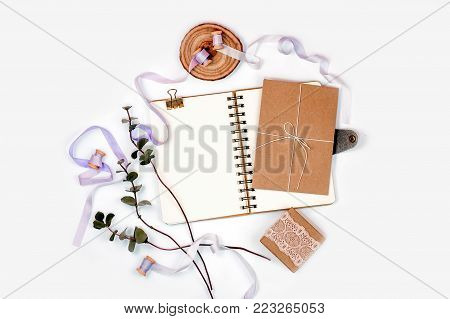 Bright composition with a spiral notebook, eucalyptus, silk ribbons and kraft paper on a white background. Photos for social media, blogs and web sites. Flat lay, top view, copy space.