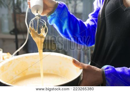 Female hands stirring dough with a mixer for cake or bread in a bowl on a kitchen worktop, preparation for baking.