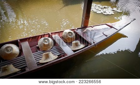 Floating Wooden Boat with Farmer's Hats Docked and Tied with Pillar
