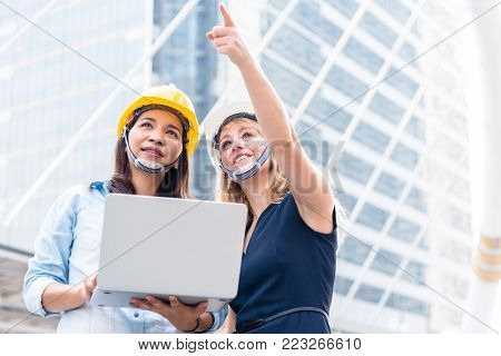 Two women engineering surveying for startup and launching new project. Building and construction concept. Business and happiness of cooperation concept. Civil engineer theme. City and urban theme