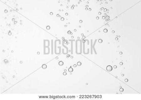 Mnay small shiny water bubbles flowing over a white background