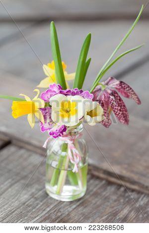 Bunch of spring flowers in litte bottle