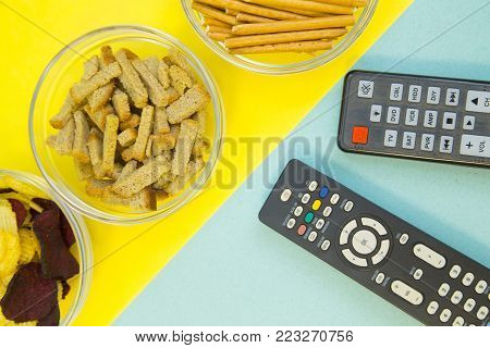 Weekend, Leisure, Lifestyle Concept. Weekend with family, two remote controls and three bowls of salty snacks on a light blue and yellow background, flat lay