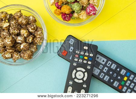 Weekend, Leisure, Lifestyle Concept. Weekend with family, two remote controls and sweet caramel popcorn on a light blue and yellow background, flat lay