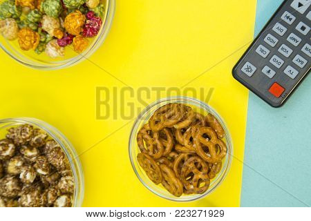 Weekend, Leisure, Lifestyle Concept. Weekend with family, a remote control, sweet caramel popcorn and salty pretzels on a light blue and yellow background, flat lay