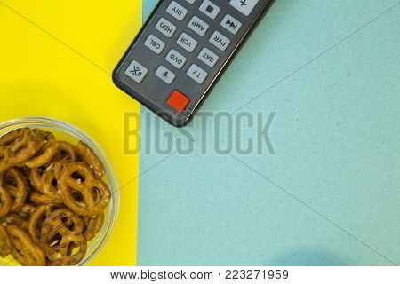 Weekend, Leisure, Lifestyle Concept. Weekend with family, a remote control and salty pretzels on a light blue and yellow background, flat lay