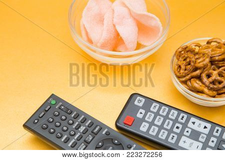 Weekend, Leisure, Hobby Concept. Weekend with movies, two remote controls, pretzels and shrimp chips on a light orange background, flat lay