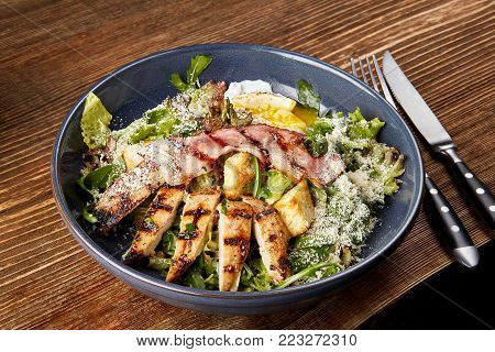 Chicken Salad. Chicken Caesar Salad. Caesar Salad with grilled chicken on plate. Grilled chicken breasts and fresh salad in plate on a wooden background. Concept restaurant menu. Still life