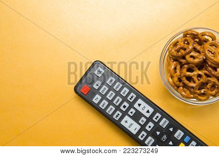 Weekend, Leisure, Hobby Concept. Weekend with movies, a remote control and pretzels on a light orange background, flat lay