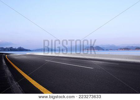 emtpy asphalt road and beautiful hangzhou qiandao lake in foggy sky